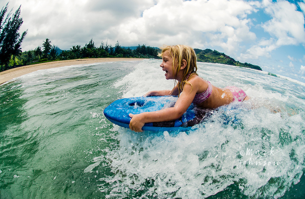 3 year old caucasian girl boogieboarding, Kauai, Hawaii