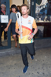 © Licensed to London News Pictures. 16/08/2017. London, UK. Longines Ambassador of Elegance Simon Baker runs with The 2018 Commonwealth Games Queen's Baton at the Longines Botique in London. The Queen's Baton Relay began its journey in Buckingham Palace earlier this year and is now travelling through 71 nations or territories of the Commonwealth, covering 230'000 kilometres<br /> Photo credit: Ray Tang/LNP