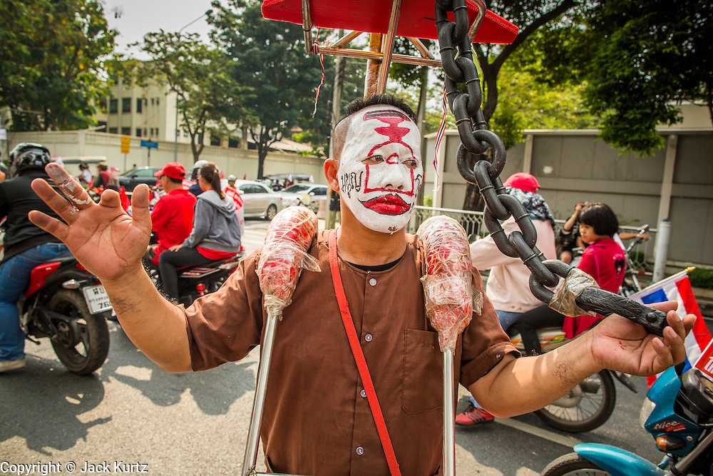 """10 DECEMBER 2012 - BANGKOK, THAILAND:    A Red Shirt protestor, shackled in chains that represent dictatorship, participates in a Red Shirt protest Monday. The Thai government announced on Monday, which is Constitution Day in Thailand, that will speed up its campaign to write a new charter. December 10 marks passage of the first permanent constitution in 1932 and Thailand's transition from an absolute monarchy to a constitutional monarchy. Several thousand """"Red Shirts,"""" supporters of ousted and exiled Prime Minister Thaksin Shinawatra, motorcaded through the city, stopping at government offices and the offices of the Pheu Thai ruling party to present demands for a new charter.      PHOTO BY JACK KURTZ"""
