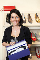 Portrait of a happy mid adult woman with footwear box in shoe store