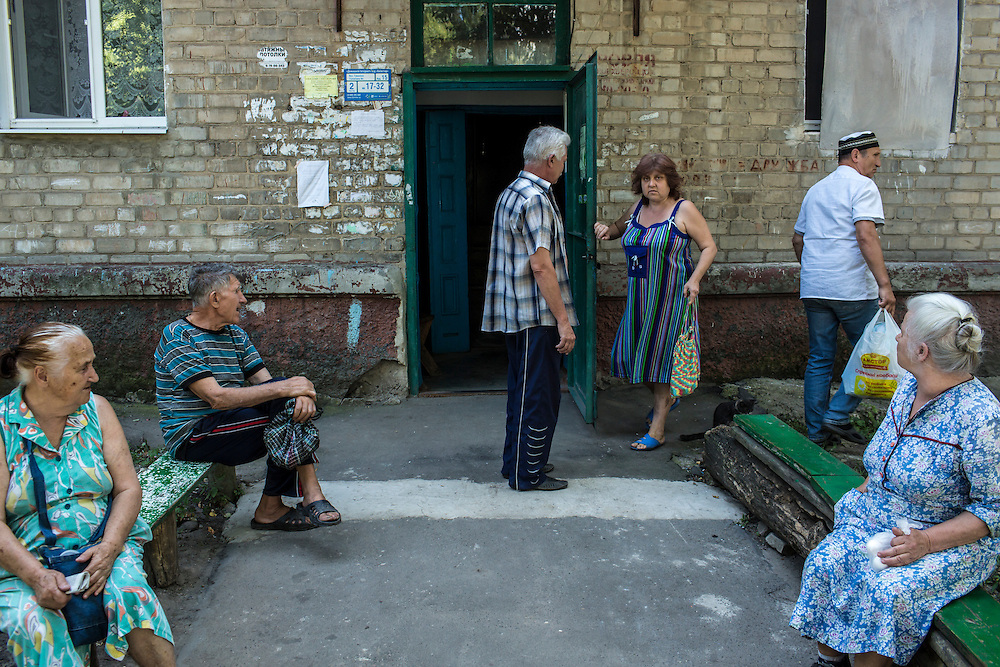 Residents of the Ploshchadka neighborhood, which has been heavily bombarded in recent days, gather outside an apartment building on Wednesday, July 30, 2014 in Donetsk, Ukraine.