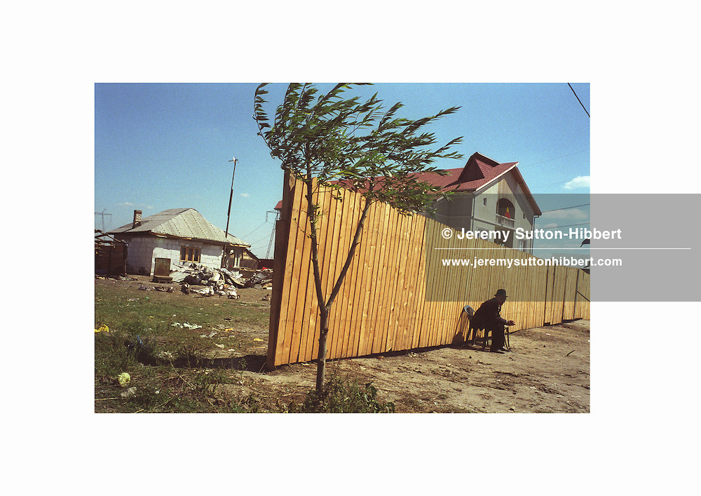 Appearances are important within the Roma community of Sintesti, so a man has built a wooden fence to stop passing cars from seeing his humble home which sits next to a large house..