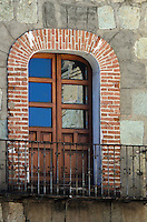 A French door opens onto a wrought iron balcony in brick and stone building, Oaxaca, Mexico.