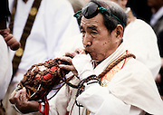 A Buddhist priest blows into an instrument made from a conch shell at a purification ceremony in which participants walk barefoot across burning embers in Takao, west of Tokyo, Japan on Sunday 09 March  2009.