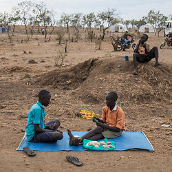 Refugee children from South Sudan play cards while selling sugar near a food distribution center in the Bidi Bidi refugee settlement in north Uganda.