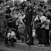 A police officer stands by children just out of school all of whom are looking at the scene of a drug related shooting of a man in front of their school yard in Culiacan, Sinaloa, Mexico..(Credit Image: © Louie Palu/ZUMA Press)
