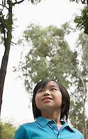 Girl (7-9) in park looking up and smiling