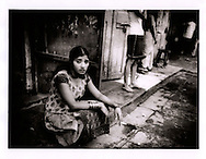 Unaffected by the economic upturn in Mumbai, India.  Worn out sex worker gazes out from her stoop on Falklands Road, the heart of the red light district, Mumbai, India.  Some sources put the level of HIV infection at 60% among Mumbai's sex workers because of low condom use.