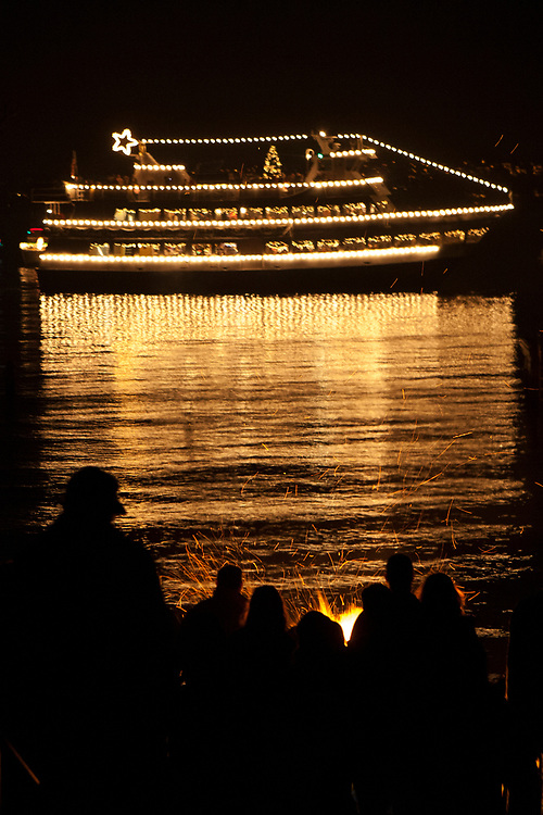North America, United States, Washington, Seattle, crowd watches Christmas Ship from beach on Lake Washington
