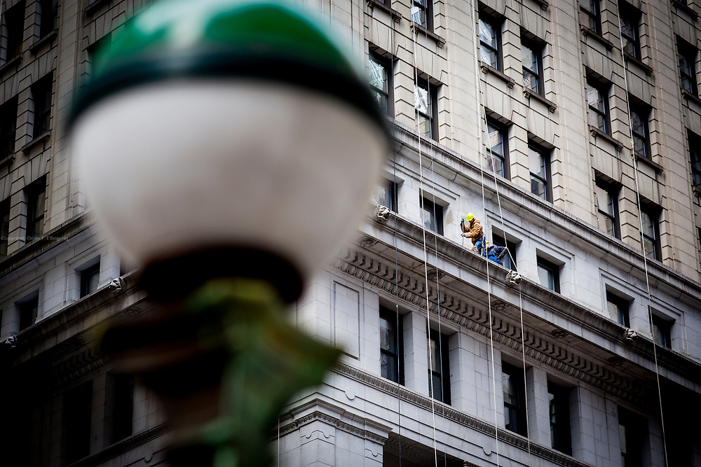 Workers fixing the facade of the 100 Broadway building, as seen from Wall Street. A gren subway entrance bulb is in the foreground.