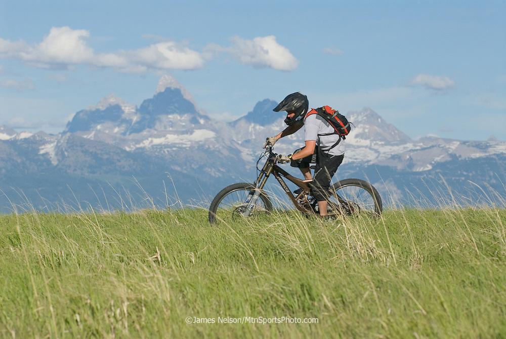 A mountain biker rides a ridgeline in the Big Hole Range of eastern Idaho, with the Teton Range of western Wyoming on the horizon.