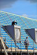 Nederland, Nijmegen, 27-2-2014Bouwplaats voor huizen in de nieuwe wijk Laauwik, onderdeel van de stadsuitbreiding Waalsprong van Nijmegen in Lent.Er worden hier veel verschillende woningtypen gebouwd, zowel voor sociale huur,koop en vrije sector. Bouwvakker, bouwvakkers, timmerman,timmerlui,timmermannen werken aan een dakkapel op het dak. Opleiding, scholing,.vakman, ambacht,vak,Foto: Flip Franssen/Hollandse Hoogte