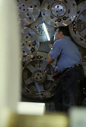 Industrial worker, large gears check checked for accuracy, printing web press for newspapers, being  inspect inspection inspecting