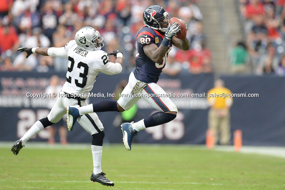 Nov. 17, 2013 - Houston, Texas, U.S - Houston Texans wide receiver Andre Johnson (80) makes a reception in front of Oakland Raiders cornerback Tracy Porter (23) during an NFL game between the Houston Texans and the Oakland Raiders at Reliant Stadium in Houston, TX on November 17th, 2013. Oakland won the game 28-23