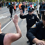 NYTRUN - NOV. 6, 2016 - NEW YORK - New York Police Department officers give our high fives as they cheer on runners in the 2016 TCS New York City Marathon in Central Park on Sunday afternoon. NYTCREDIT:  Karsten Moran for The New York Times