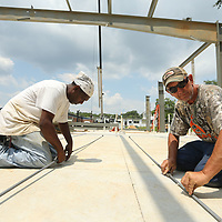 Reggie Allen and Sam Hollis, workers with Southland Construction in Tupelo, connect X braces that will be used to secure the cieling beams on the new construction of the homeless shelter, The Red Shield Lodge, at the Salvation Army in Tupelo on Tuesday afternoon.