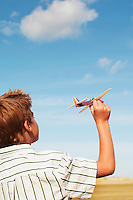 Boy standing on beach Flying Toy Airplane back view