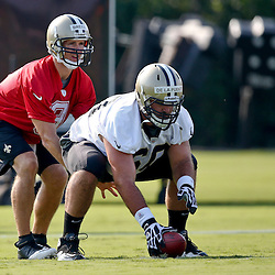 Jul 26, 2013; Metairie, LA, USA; New Orleans Saints quarterback Drew Brees (9) under offensive guard Brian De La Puente (60) during the first day of training camp at the team facility. Mandatory Credit: Derick E. Hingle-USA TODAY Sports