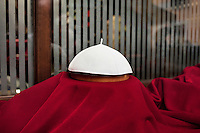 ROME, ITALY - 12 MARCH 2013: An example of a zucchetto, an ecclesiastical skullcap worn by popes, is on display in the shop window of the Gammarelli tailor shop, a family owned business since 1798 working for the Roman clergy, that has dressed popes for generations, in Rome, Italy, on March 12, 2013...On March 12, 2013, the 115 cardinals are set to enter the conclave to elect a successor to Pope Benedict XVI after he became the first pope in 600 years to resign from the role. The conclave will take place inside the Sistine Chapel and will be attended by 115 cardinals as they vote to select the 266th Pope of the Catholic Church.