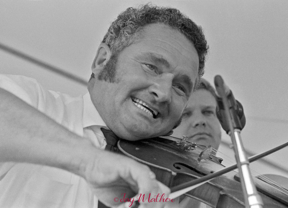 The Second Annual Adams County Bluegrass Festival, August 23-25, 1974. Performers included Bill Monroe &amp; the Blue Grass Boys &bull; Ralph Stanley &bull; Lester Flatt &bull; James Monroe &bull; Bluegrass Alliance &bull; Country Gazette &bull; Bobby Smith &bull; Monroe Doctrine &bull; The McLain Family Band &bull; Clyde Moody &bull; Haystack Mountain Boys &bull; Denver Grass &bull; City Limits &bull; Possumtrotters &bull; Colorado Sage &bull; Dudley Murphy &bull; Ray &amp; Ina Patterson &bull; Williams Family &bull; Minnie Moore.<br /> <br /> The festival continued at this venue through 1987. After that it was held in Loveland, Colorado for four years before relocating again to Lyons, Colorado in 1992 where the event has been held for the past 25 years.<br /> <br /> Curly Ray Cline playing fiddle.