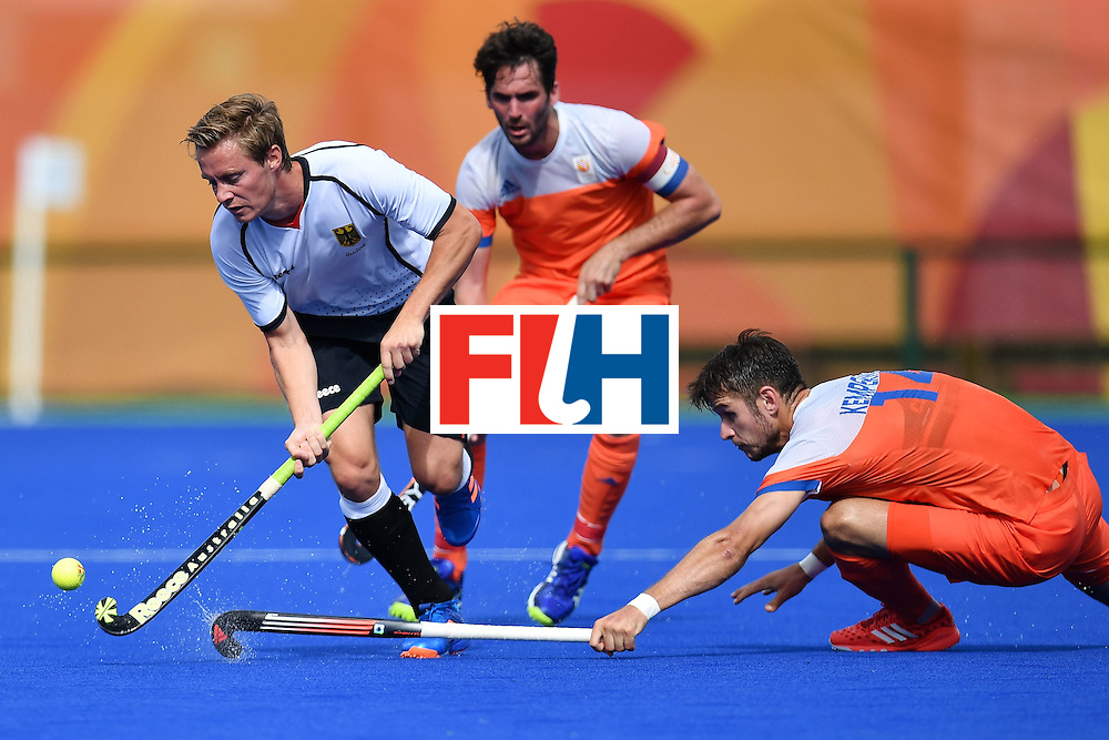 Germany's Mats Grambusch (L) is tackled by Netherlands' Robbert Kemperman during the mens's field hockey Germany vs Netherlands match of the Rio 2016 Olympics Games at the Olympic Hockey Centre in Rio de Janeiro on August, 12 2016. / AFP / MANAN VATSYAYANA        (Photo credit should read MANAN VATSYAYANA/AFP/Getty Images)