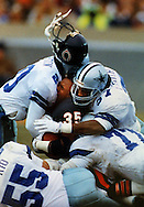 Neal Anderson of the Chicago Bears gets crushed between two Dallas Cowboys.--1991 NFC playoffs