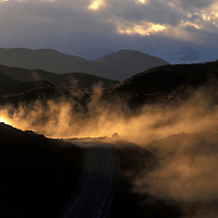 Chile, Torres del Paine National Park, Van raises cloud of dust driving on gravel road at sunset