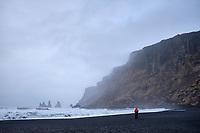 Tourist at Víkurfjara, black sand beach at Vík, South Iceland.