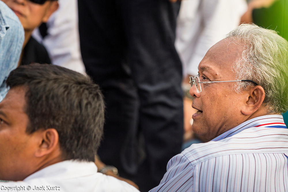 """09 DECEMBER 2013 - BANGKOK, THAILAND: SUTHEP THAUGSUBAN, former Deputy Prime Minister of Thailand and leader of anti-government protests, meets with other protest leaders in front of Government House in Bangkok. Thai Prime Minister Yingluck Shinawatra announced she would dissolve the lower house of the Parliament and call new elections in the face of ongoing anti-government protests in Bangkok. Hundreds of thousands of people flocked to Government House, the office of the Prime Minister, Monday to celebrate the collapse of the government after Yingluck made her announcement. Former Deputy Prime Minister Suthep Thaugsuban, the organizer of the protests, said the protests would continue until the """"Thaksin influence is uprooted from Thailand."""" There were no reports of violence in the protests Monday. The collapse of the government leaves Thailand with an unprecedented power vacuum.      PHOTO BY JACK KURTZ"""