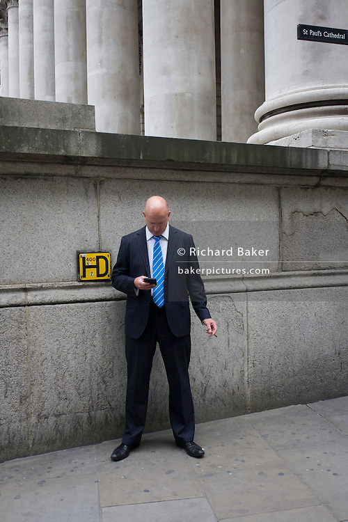 Pinstriped suit businessman checks messages during a cigar break, beneath tall of columns at Cornhill, City of London.