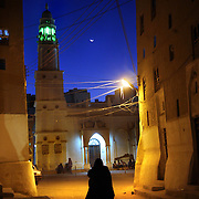 A woman walks towards a mosque at dusk in Shibam. Shibam, a fortified 16th century city is one of the oldest and best examples of urban planning based on the principle of vertical construction. The tower like buildings have been dubbed 'the Manhattan of the desert'.
