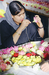 Young Asian woman making garlands for the Baisakhi festival,