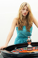Young woman standing at roulette wheel