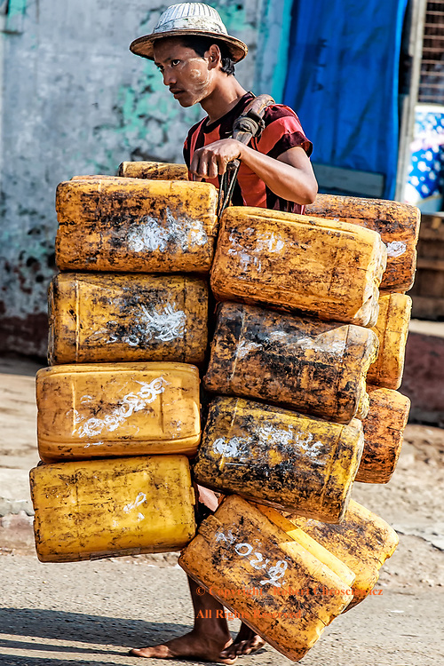 Barefoot Porter: A young barefoot man uses a yoke to carry a multitude of large, soiled yellow containers down the road in an intense tropical heat, harbour side in Yangon Myanmar.