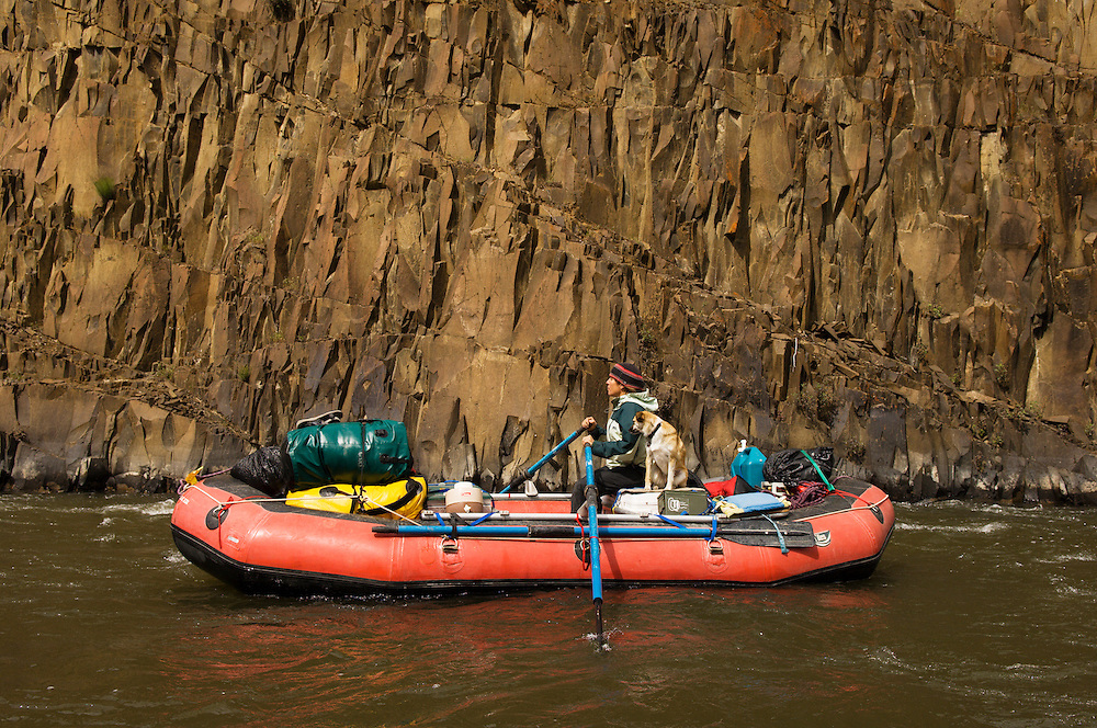Young woman and dog on inflatable raft on the John Day River, Oregon.