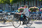 Young woman wearing high heels shoes and headphones  cycling out for evening across bridge in Amsterdam, Holland