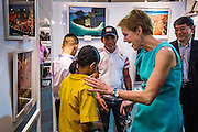 19 JULY 2013 - BANGKOK, THAILAND:  KRISTIE KENNEY, the US Ambassador to Thailand, talks to a Thai school girl at the opening of a photo exhibit sponsored by the US Embassy in Bangkok. The photo exhibit celebrates 180 years of US-Thai diplomatic relations. There are 180 photos hanging in the show, 90 by American photographers in Thailand and 90 by Thai photographers in the United States. The show, which opened July 19, is hanging in CentralWorld, a large mall in Bangkok, and is touring Thailand when it concludes its Bangkok run on July 21.    PHOTO BY JACK KURTZ