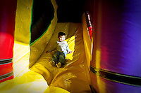 Aiden Kilpatrick, 3, descend's down one of the inflatable bounce house slides Tuesday at Bounce Party in Post Falls.
