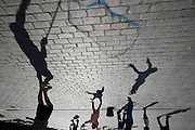 Children jumping with bubbles and shadows.Plaza del Salvador, Seville, Andalucia, Spain.<br /> Photo: Zute Lightfoot