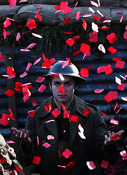 Poppies fall on actor James Dutton during the launch of the Poppyscotland fundraising challenge The 1918 Poppy Pledge. They are seen in a recreated First World War trench at Pollok Country Park in Glasgow.