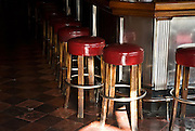 San Francisco, California, July 20, 2008-A row of bar stools at Tosca Cafe. For almost 80 years this bar has remained untouched. Two large, antique espresso machines, a long bar, original red vinyl booths, and a vintage jukebox with the original records all lie within the historic deco structure.