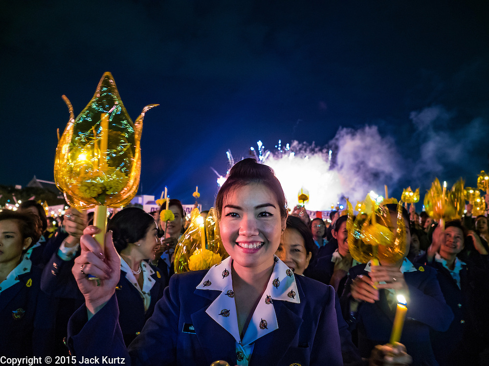 05 DECEMBER 2015 - BANGKOK, THAILAND: Thais hold up candles during the King's Birthday on Sanam Luang in Bangkok. Thais marked the 88th birthday of Bhumibol Adulyadej, the King of Thailand,  Saturday. The King was born on December 5, 1927, in Cambridge, Massachusetts. The family was in the United States because his father, Prince Mahidol, was studying Public Health at Harvard University. He has reigned since 1946 and is the world's currently the longest serving monarch in the world and the longest serving monarch in Thai history. Bhumibol, who is in poor health, is revered by the Thai people. His birthday is a national holiday and is also celebrated as Father's Day. He is currently hospitalized in Siriraj Hospital, recovering from a series of health setbacks.    PHOTO BY JACK KURTZ