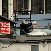 NLD/Amsterdam/20061220 - Cabaratier Youp van 't Hek voor zijn huis Prinsengracht Amsterdam, met Ikea glazen