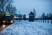 A Public bus transporting visitors in between Auschwitz and Auschwitz Birkenau at the Auschwitz Birkenau Nazi concentration camp gate. It is estimated that between 1.1 and 1.5 million Jews, Poles, Roma and others were killed in Auschwitz during the Holocaust in between 1940-1945.