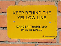 Keep behind the yellow line sign in train station