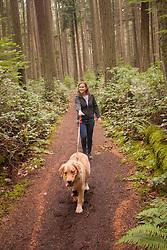 United States, Washington, Kirkland, woman walking golden retreiver dog in forest of Bridle Trails State Park.  MR
