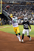 Green Bay Packers rookie wide receiver Marquez Valdes-Scantling (83) leaps in the air while trying to catch an incomplete end zone pass while covered by Oakland Raiders rookie cornerback Nick Nelson (38) the 2018 NFL preseason week 3 football game against the Oakland Raiders on Friday, Aug. 24, 2018 in Oakland, Calif. The Raiders won the game 13-6. (©Paul Anthony Spinelli)