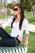 Young Female At The Park Enjoying IPod