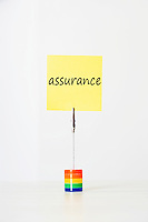 Sticky notepaper with French text Insurance clipped to a multicolored card holder