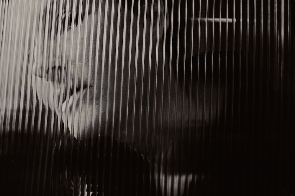 A young womans face behind corrugated glass